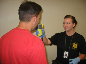 A Probation Officer administers a test that checks for alcohol on an offender.