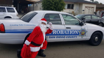 Santa Claus with his toy bag outside a San Diego County Probation car.