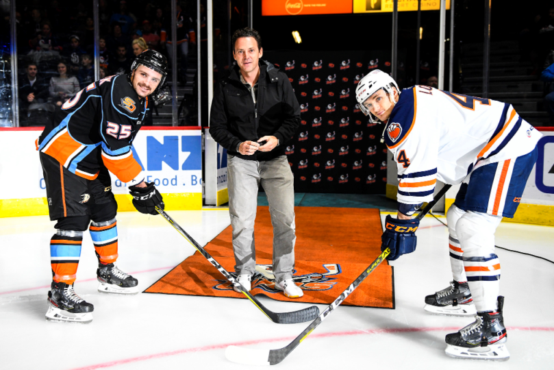 Two ice hockey players wait for the puck drop
