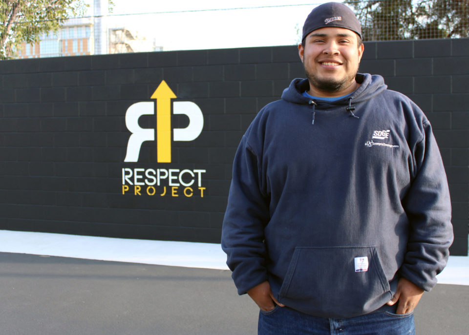 RESPECT Project graduate Antonio Ramirez stands in front of the RESPECT Project logo