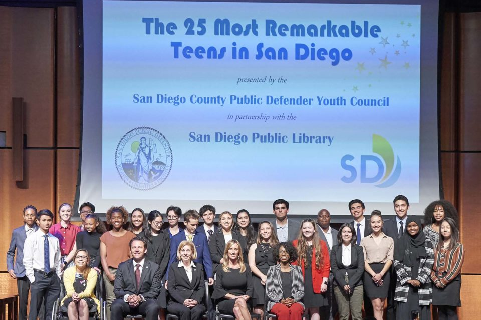 Group photo of 25 teens honored for their accomplishments on stage with award presenters.