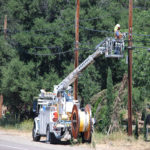 Utility workers repairing damaged electric lines.
