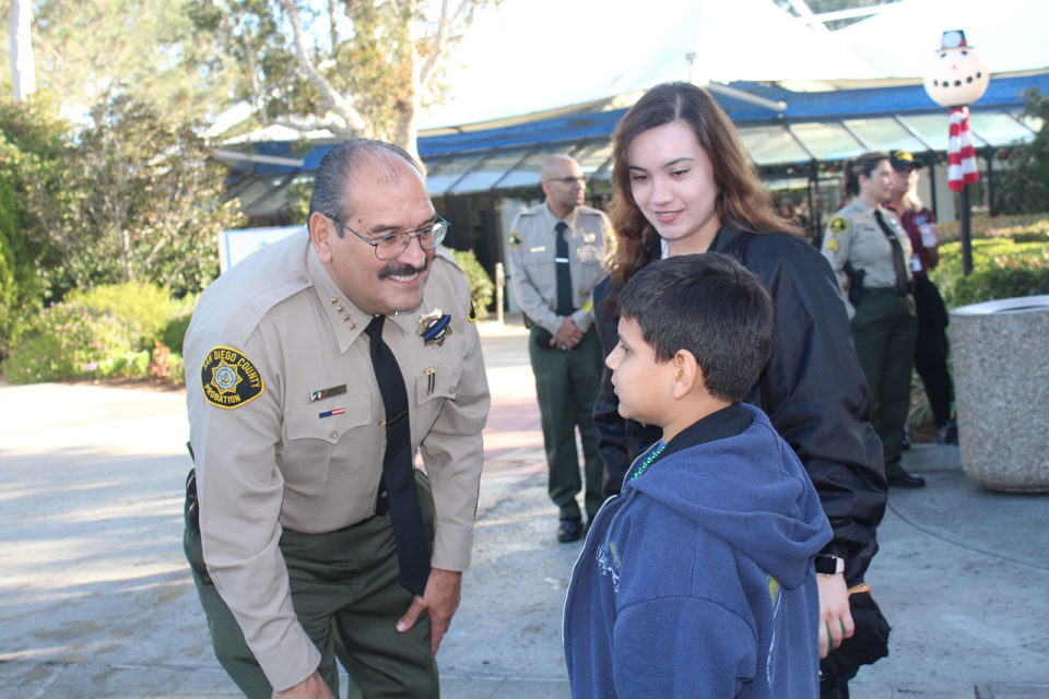Chief Probation Officer Adolfo Gonzales greets a child who was paired up with one of his officers.