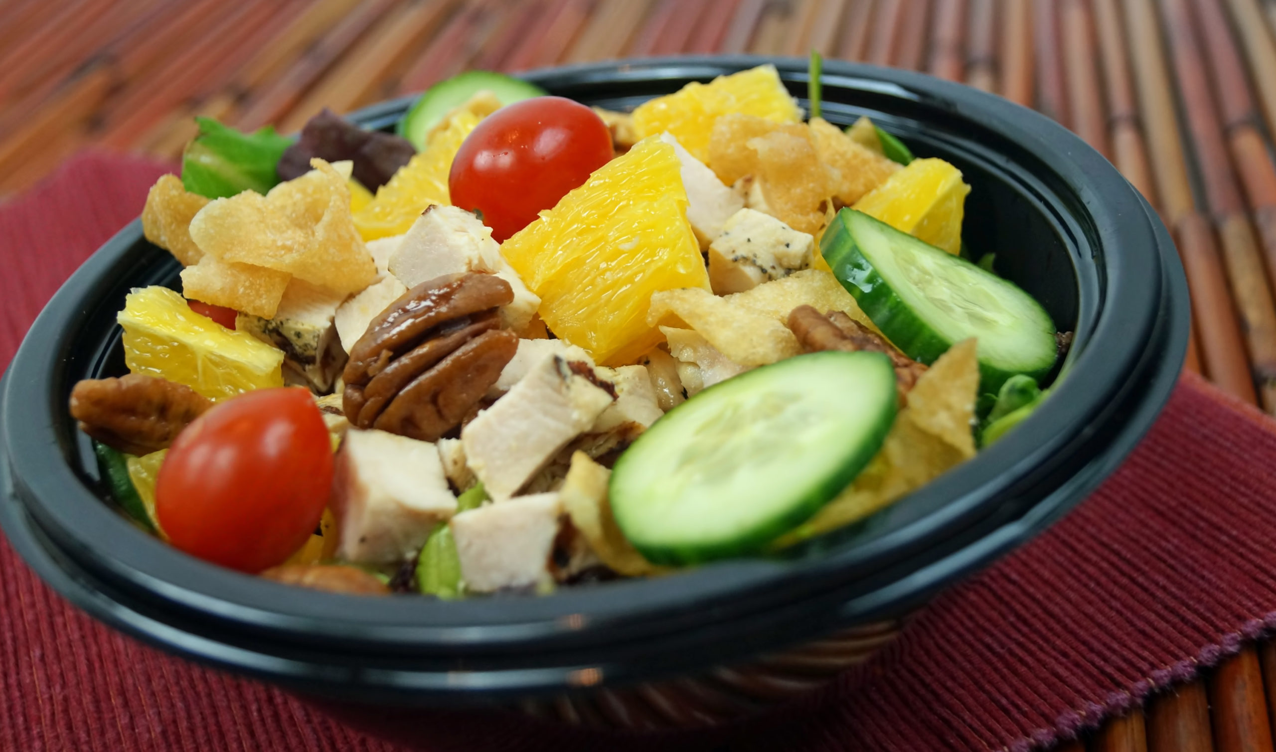 A bowl of salad in a take out container