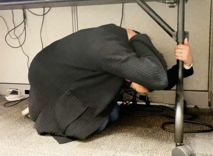 Employee under a desk covering head for earthquake drill.