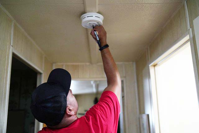 Man tests a smoke alarm by pushing the test button.