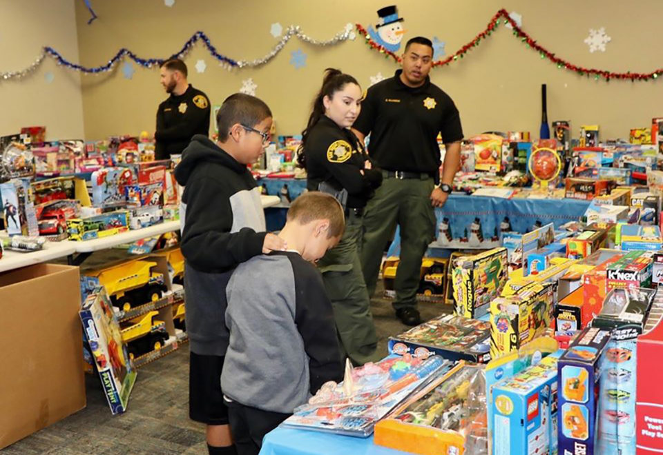 Two young boys select a toy from a toy display and get help from Probation officers.