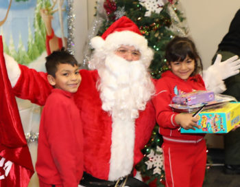 A young boy and girl pose with Santa while holding their new toy.