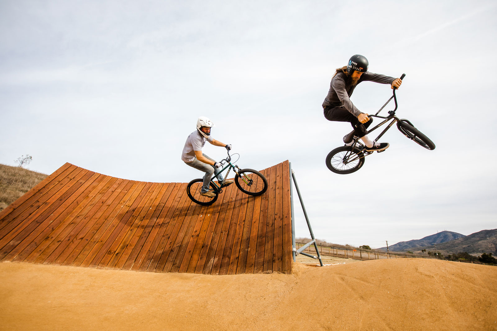 Two mountain bike riders on a jump track. One catching air.