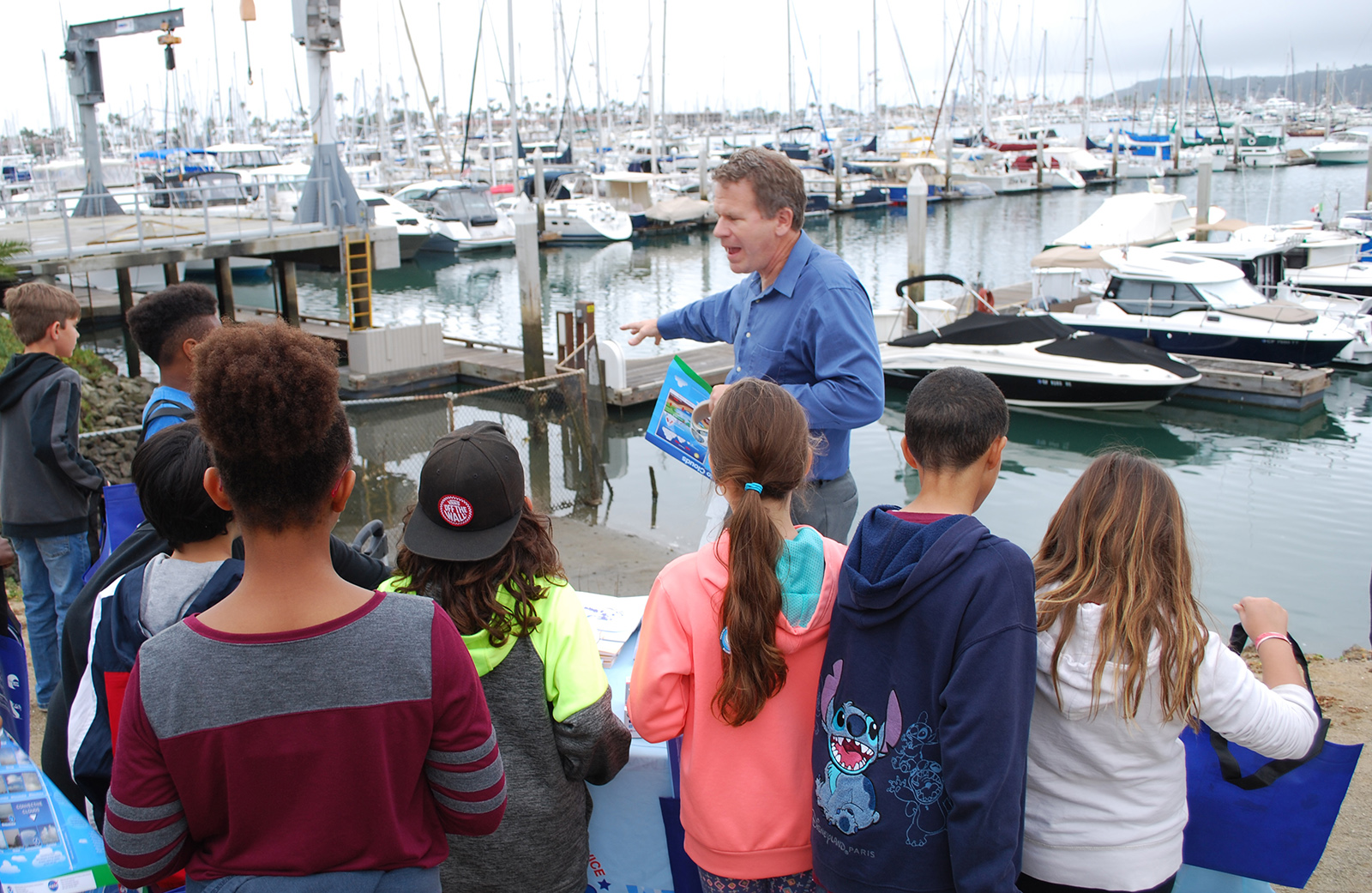 Meteorologist Alex Tardy with the National Weather Service San Diego office talks to Cabrillo fourth graders about how being in a boat in a marina is an unsafe place to be during a tsunami because they will all get knocked around and collide.