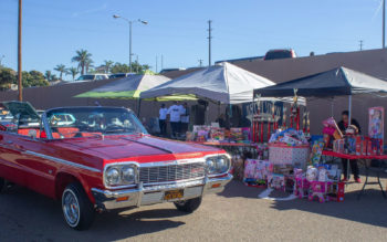 A red lowrider car parked in front of several tables with donated toys at a previous year's event.