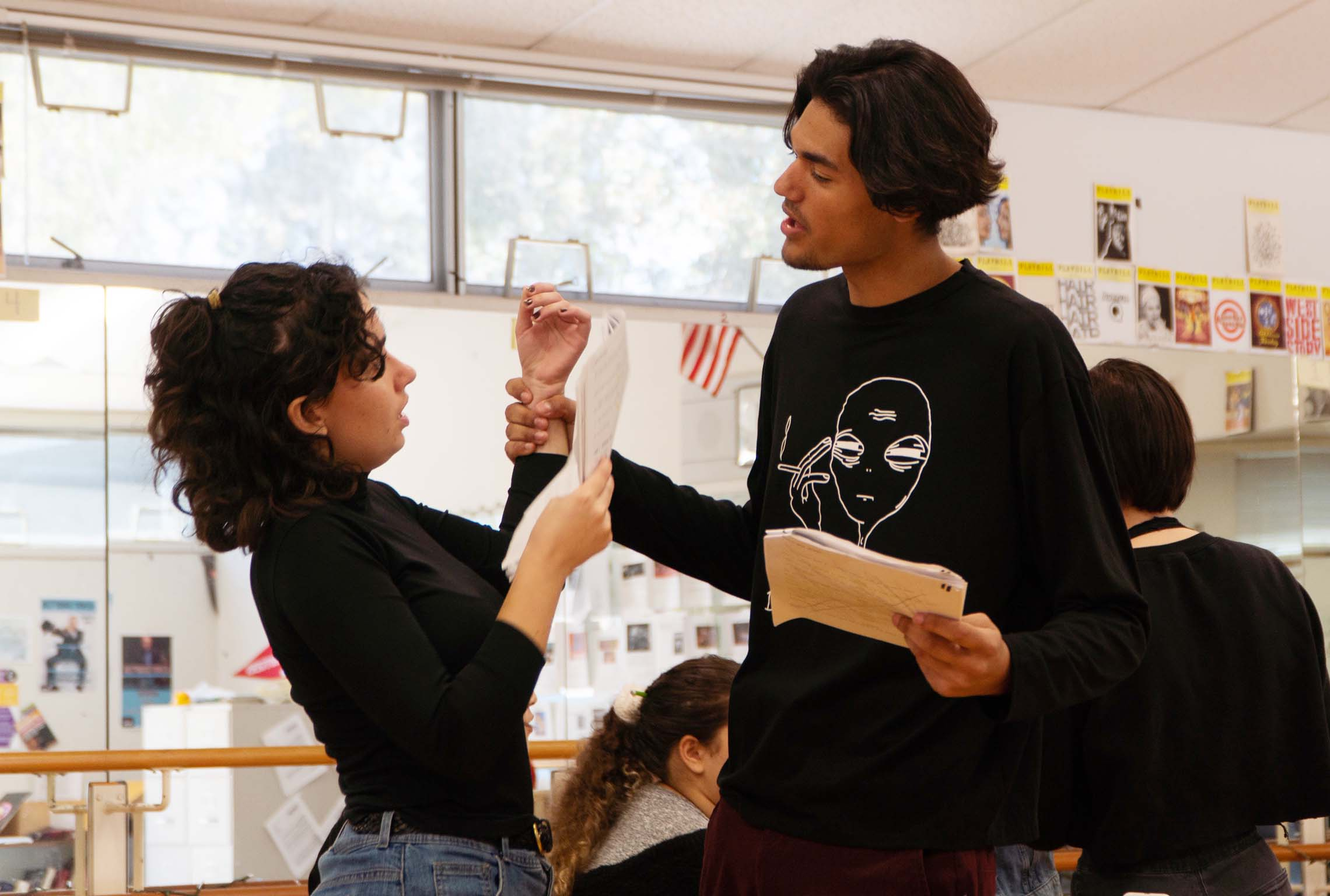 A teenage actor grabs a teenage actress' wrist in a threatening manner while practicing a scene from a play about human trafficking.