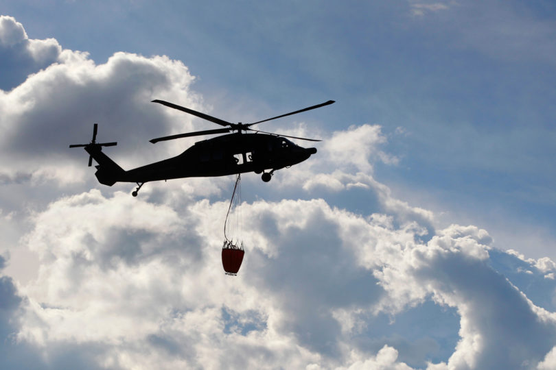 Stock photo of a UH-60 Black Hawk helitanker in the air hoisting a water bucket.