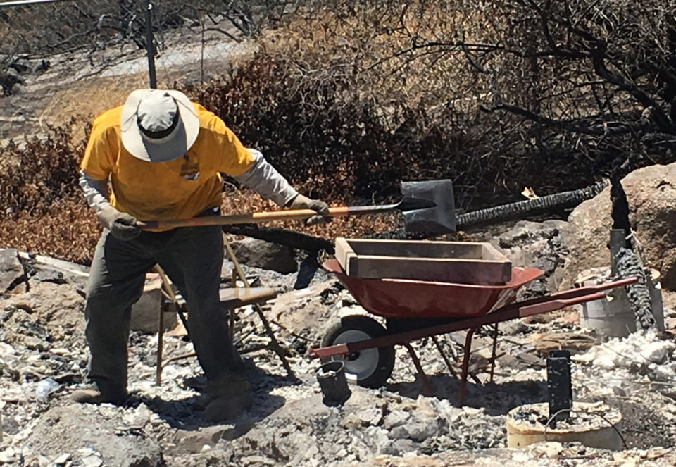 A member of the California Southern Baptist Disaster Relief team work on cleaning up debris on a property burned during the Potrero Fire.
