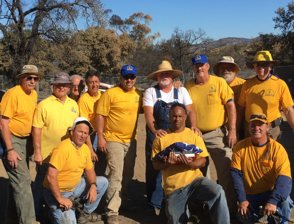 The California Southern Baptist Disaster Relief group pose with Potrero Fire survivor Bill Cronkrite whose home was burned. They helped with debris removal on his property.