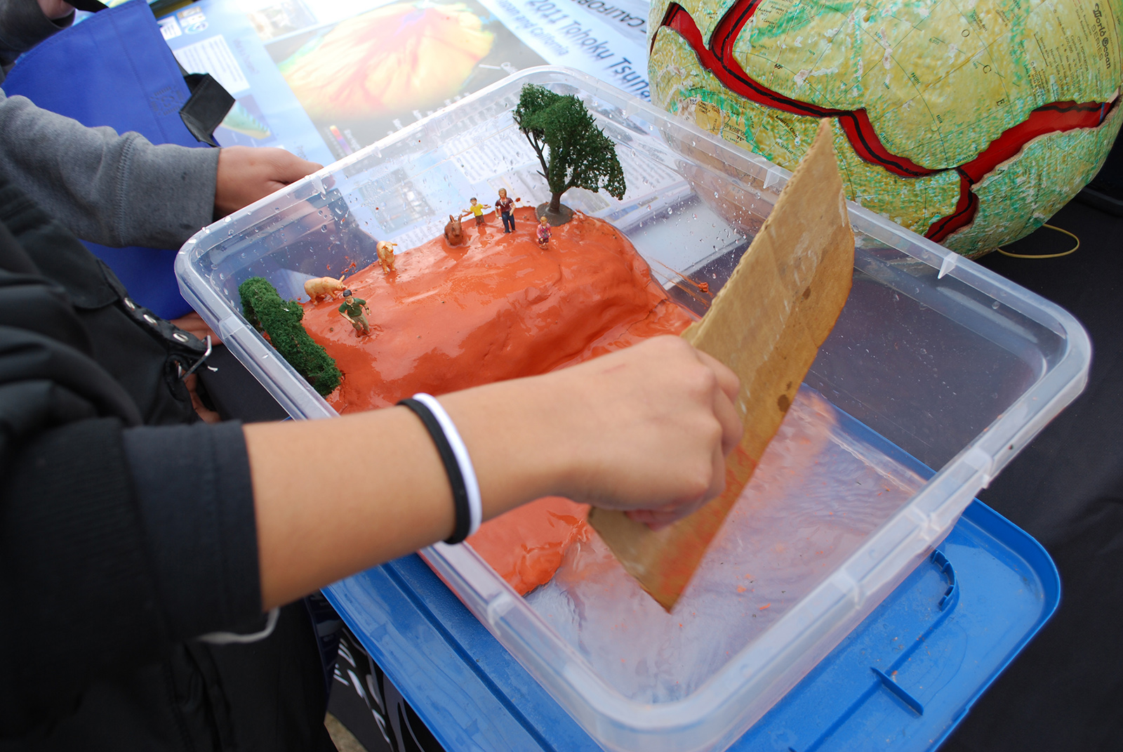A student uses the cardboard to show how water will move surge forward toward land in this model.