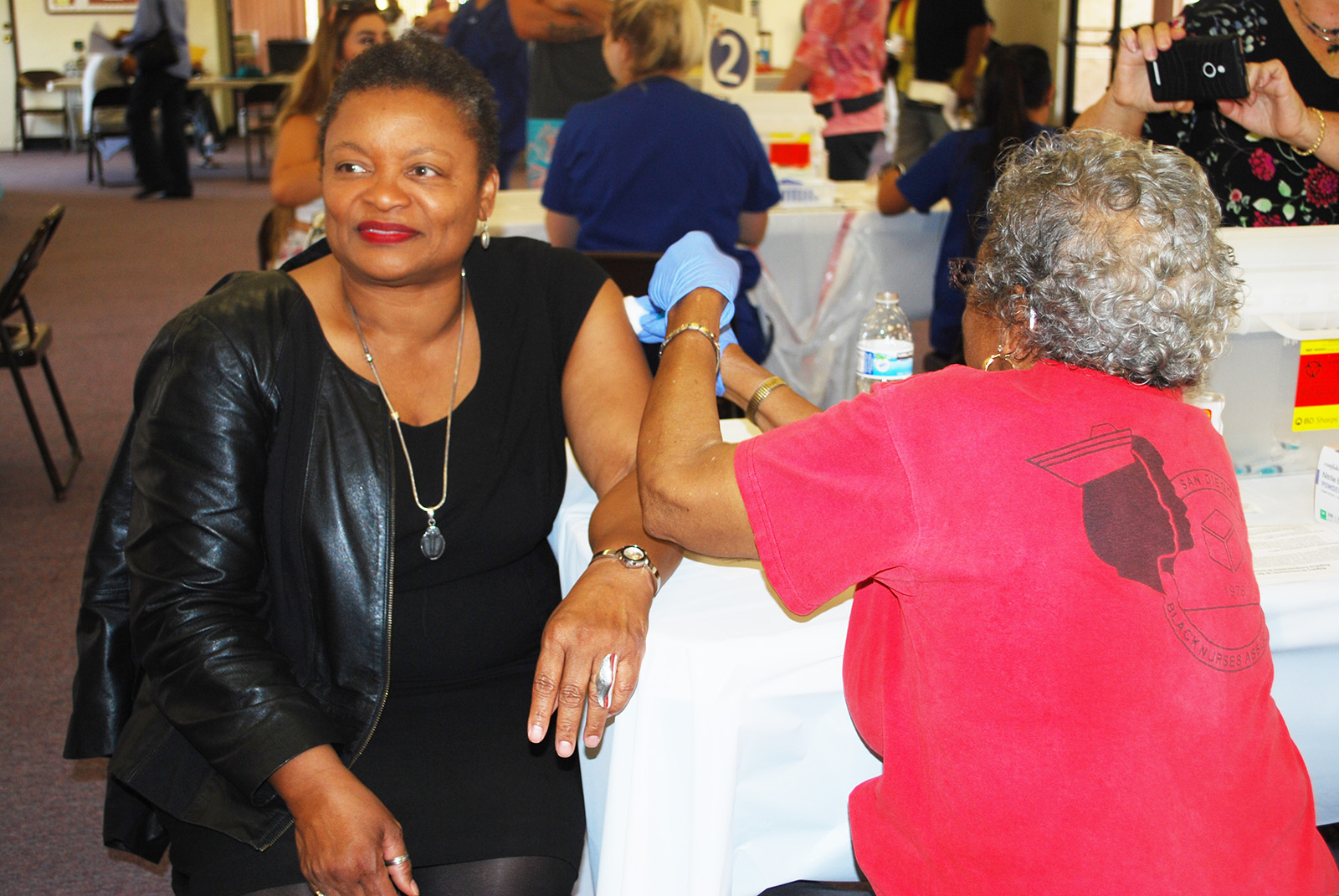 County Public Health Officer Dr. Wilma Wooten gets vaccinated by Syvera Hardy from the San Diego Black Nurses Association.