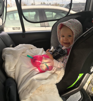 Infant sitting in a rear-facing car seat.