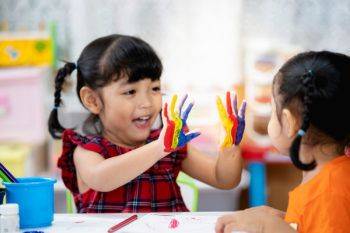 Pre-school girl shows painted hands to another girl.