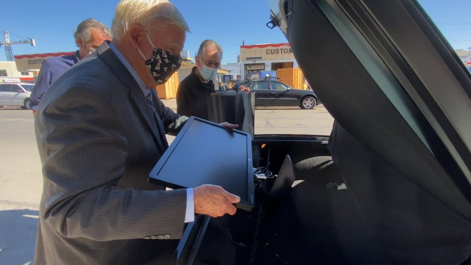 Supervisor Greg Cox places a computer into the truck of a car