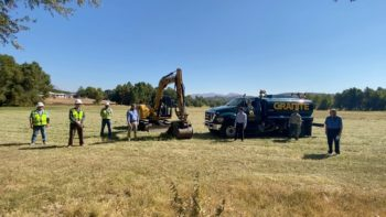 construction workers in a field with a backhoe