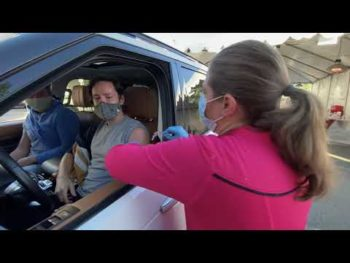 nurse gives vaccination to person in car