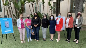 group of woman stand outside County Administration Center with masks on