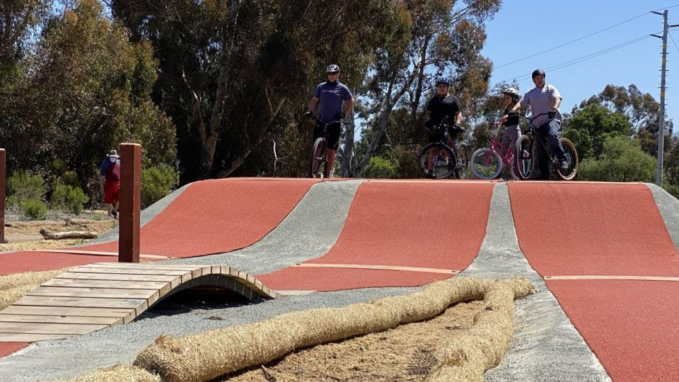 four people on bicycles wait to ride on the pump track