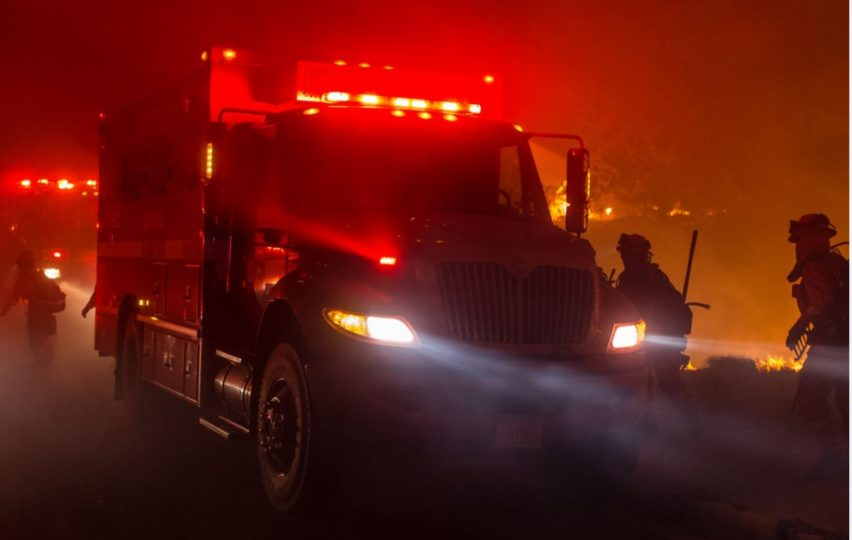 Fire engine at night with lights on and red glow behind.