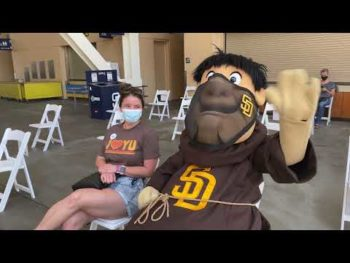 Padres Friar and a young female wear masks outside Petco Park