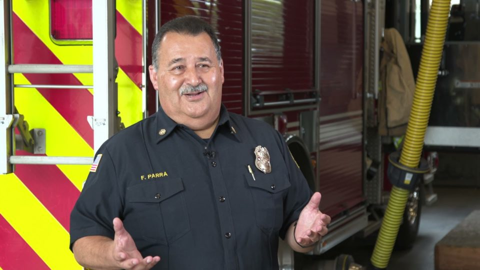 Chief Parra stands in front of a fire engine
