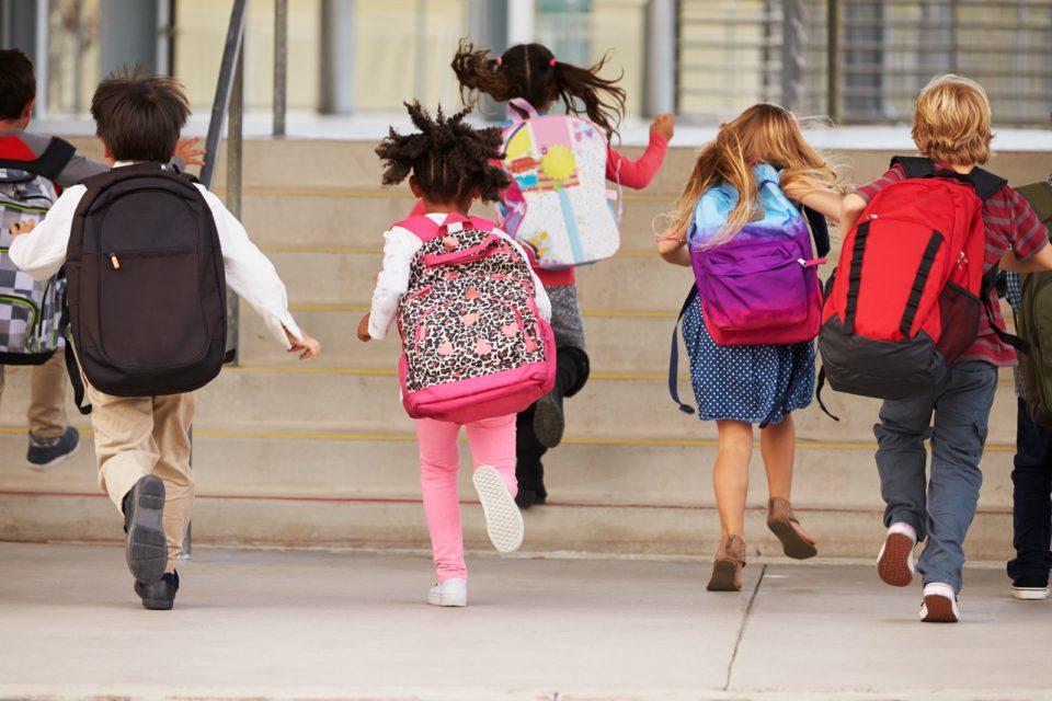 children wearing backpacks and running