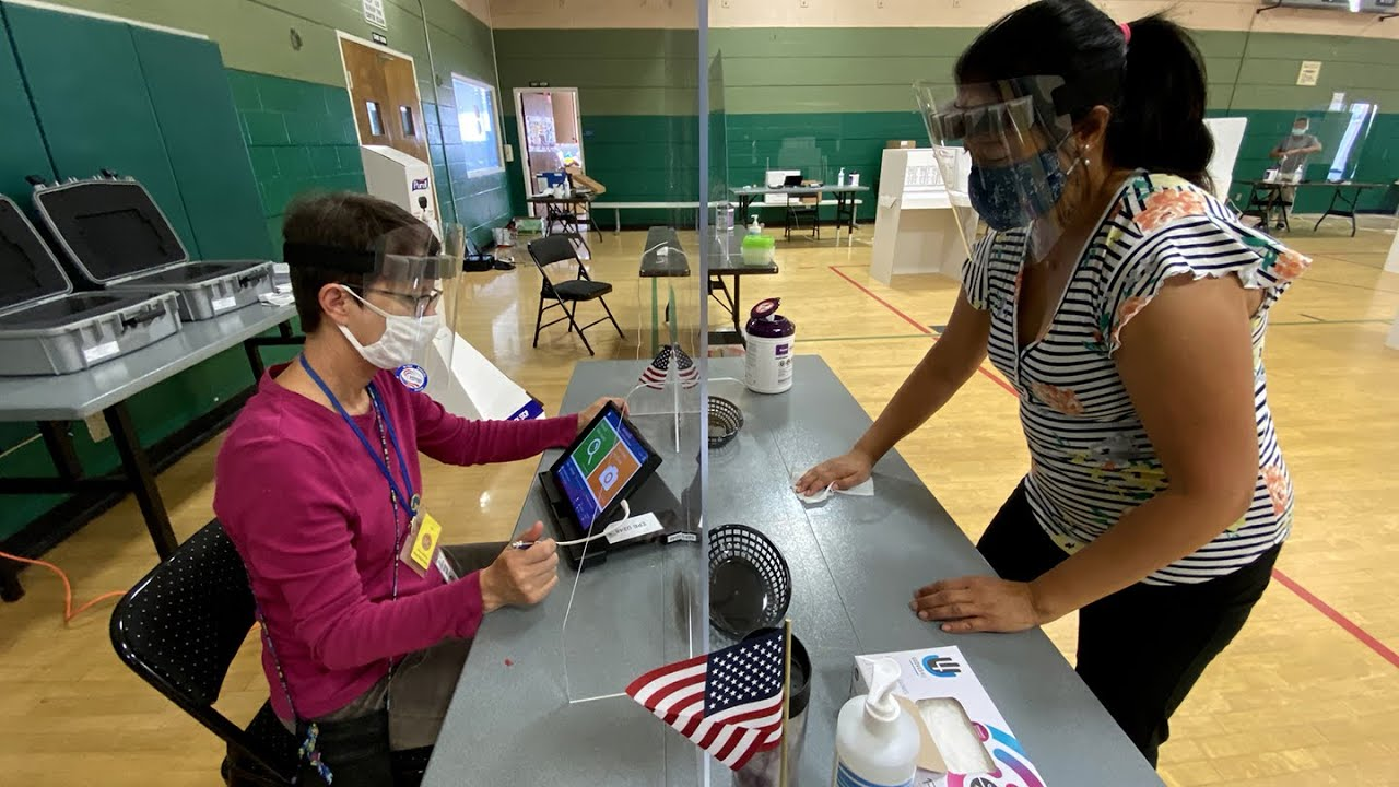 poll workers with masks and face shields keep a polling place clean