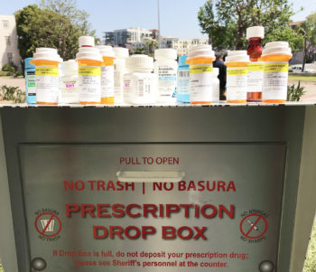 Picture of a Sheriff's Prescription Drug Drop Box with medication bottles on top.
