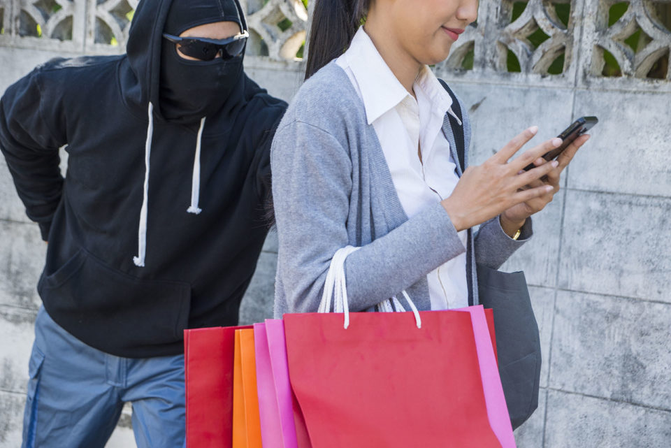 A thief sneaks up on a distracted lone shopper walking back to her vehicle.