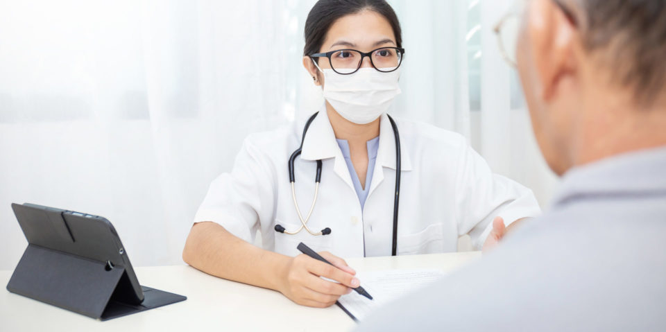 doctor with a mask on speaks to a patient