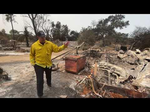 Burned home with man surveying damage.
