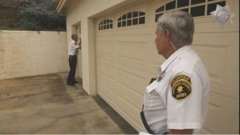 Sheriff Senior Volunteer Patrol members check to make sure the garage doors are secure as part of a free vacation check service. The patrol checks the entire exterior of a home.