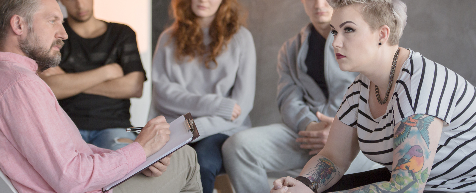 Teenage girl listening to a counselor in a circle with others.