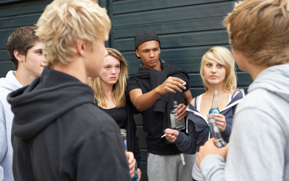 Teenagers standing around drinking alcohol and smoking