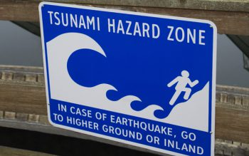 Sign that reads Tsunami Hazard Zone advising people to move away from water