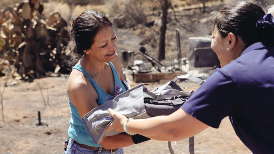 A woman who lost her home and all her belongings in the Border Fire accepts a blanket from a Tzu Chi team member. The woman, who also lost her home in 2007 and was helped by Tzu Chi, told members she hopes to help others by volunteering with Tzu Chi after she settles into a new home.