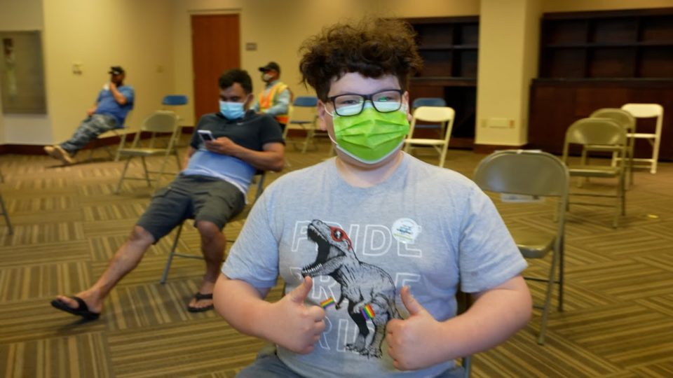 child with mask on gives two thumbs up